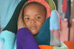 A small child wrapped in a blanket purchased from the Swop Shop
